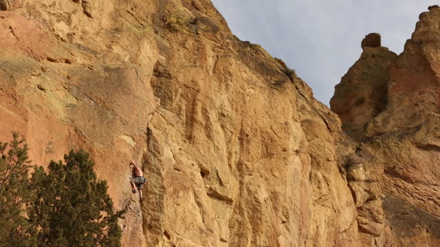 People practicing rock climbing inside of Smith Rock State Park on a sunny day.