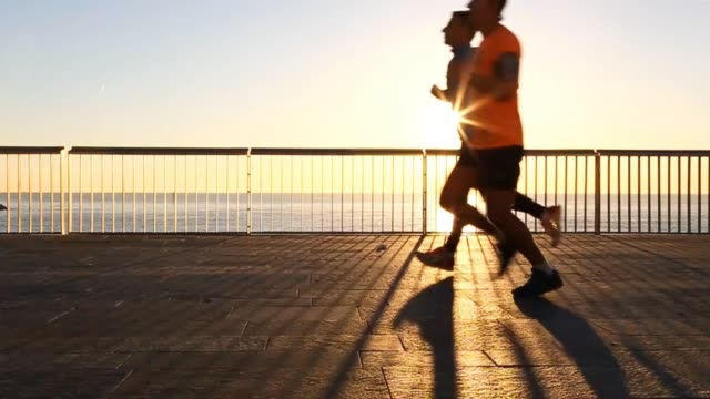 vídeos y material grabado en eventos de stock de people practicing sports and running on the very first light of the morning in the barcelona shoreline boardwalk with the beach and the sunrise over... - bulevar
