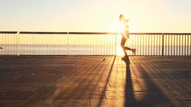 vidéos et rushes de people practicing sports and running on the very first light of the morning in the barcelona shoreline boardwalk with the beach and the sunrise over... - allée couverte de planches