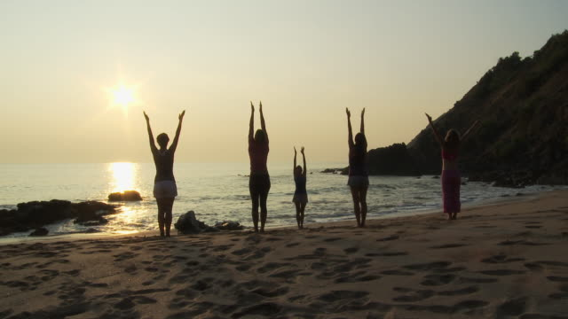 People practicing yoga on beach at sunset