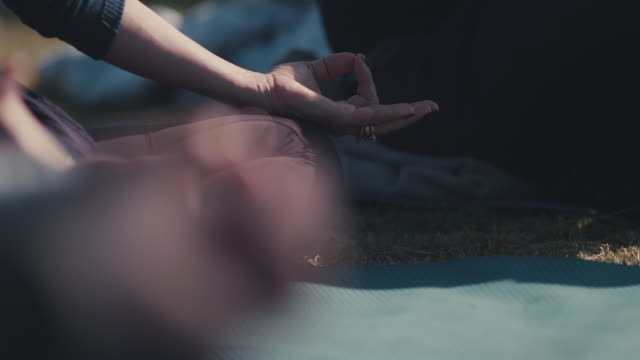 vídeos de stock, filmes e b-roll de people practicing yoga outside - posição de lótus