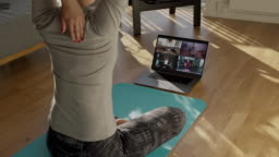 People practicing yoga with trainer via video conference