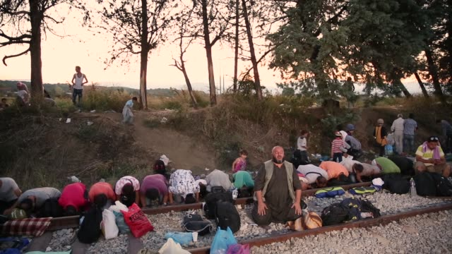 People pray at sunset as families wait along with hundreds of other on train tracks at the Greek Macedonian border on September 2 2015 in Idomeni...