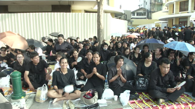 people pray close to the sanam luang where the funeral and cremation of the late king of thailand bhumibol adulyadej - king of thailand stock videos and b-roll footage