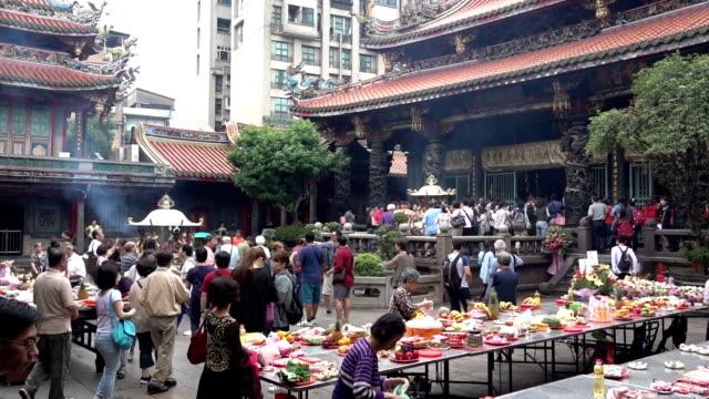 台湾台北市の龍山寺で祈る人々