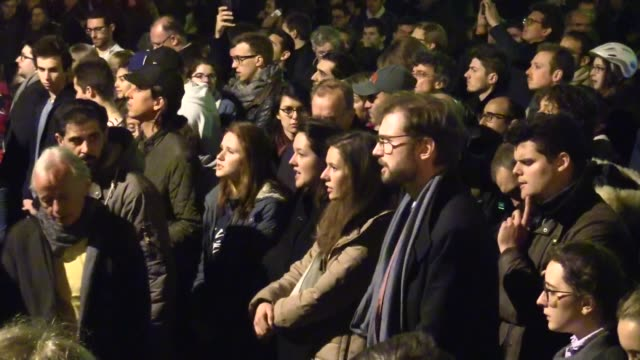 people praying and singing while notre dame cathedral is burning in paris on april 15, 2019 in paris, france. a fire broke out on monday afternoon... - notre dame de paris stock videos & royalty-free footage