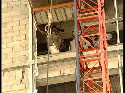 vídeos y material grabado en eventos de stock de people praying at mosque / workmen on building site / jeddah night scenes workmen on building site and on lift / lift carrying men up sode of... - jeddah