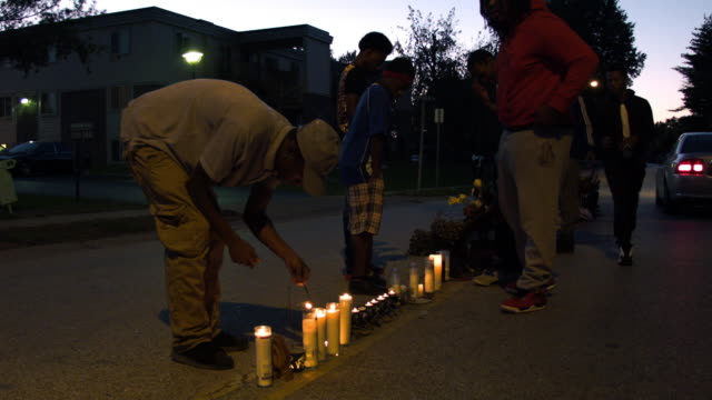 People protest across the street from the Ferguson Police department in the city where police and protesters clashed over a number of days after the...