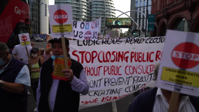 people protesting about roads being closed to traffic without public consultation - banner sign stock videos & royalty-free footage