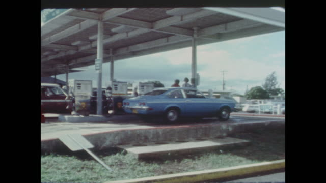People pump gas into their cars during oil embargo