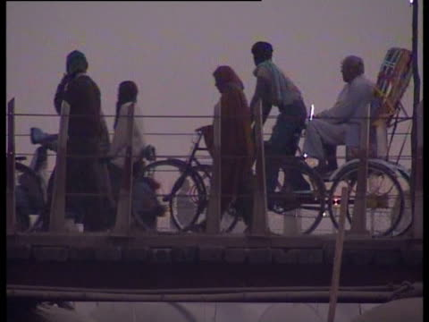 people push bicycles and rickshaw across a bridge during the maha kumbh mela - riksha bildbanksvideor och videomaterial från bakom kulisserna