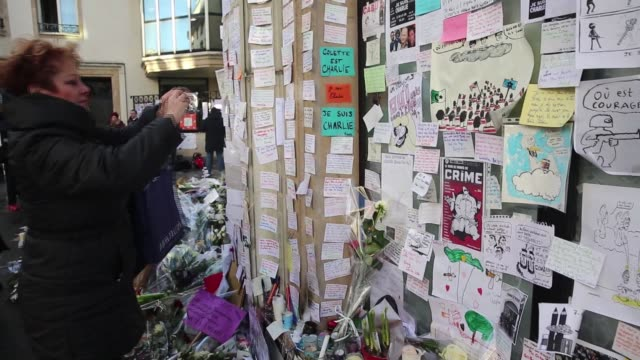 people put flowers and light candles outside the charlie hebdo magazine office at rue nicolasappert street to commemorate the victims killed in last... - temporäre gedenkstätte stock-videos und b-roll-filmmaterial