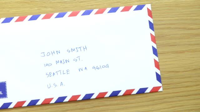 vídeos de stock, filmes e b-roll de cngloth97-pessoas colocando selos em letra e pacotes - nota mensagem