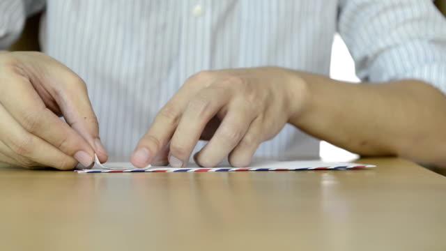 vídeos de stock e filmes b-roll de cngloth97-pessoas colocando marcas de letra e embalagem - selo postal