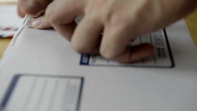 cngloth97-personen-putting-briefmarken auf buchstabe und package - post stock-videos und b-roll-filmmaterial