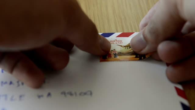 cngloth97 -人でパッティングスタンプ文字とパッケージ - 郵便切手点の映像素材/bロール