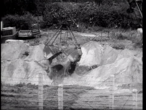 people putting up barbed wire as initial berlin wall is built/ dragline dumping dirt during construction of ditch/ guard pacing beside destroyed... - 1961 stock videos & royalty-free footage