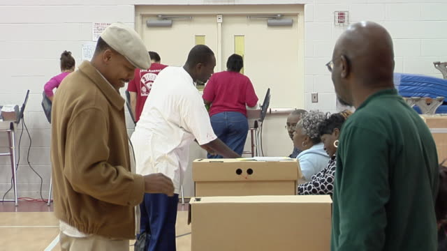 MS, People putting voting ballots into ballot boxes, Toledo, Ohio, USA