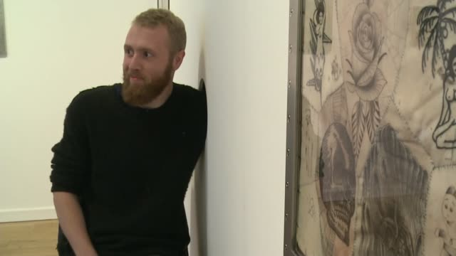 People queue for mystery tatoos by artist Scott Campbell ENGLAND London INT Various of Cameron Ward with arm through gallery wall Man taking raffle...