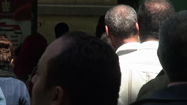 people queue up and wait to vote, show the ink on their fingers as proof of voting and hold up their identity cards in the constitution referendum on... - ink stock videos & royalty-free footage