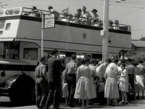 people queue up to board a sightseeing bus on bournemouth seafront - bournemouth england stock videos & royalty-free footage