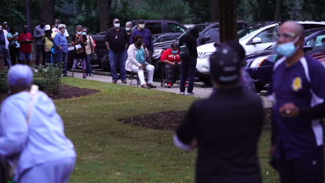 people queueing outside of a polling place on the first day of early voting in atlanta, georgia, u.s. on monday, october 12, 2020. - atlanta georgia stock videos & royalty-free footage