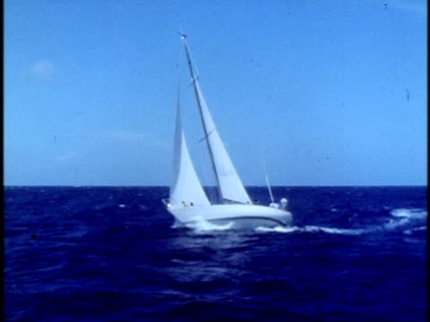 1975 MONTAGE MS People racing in sailboat during yacht regatta off coast of Oahu/ WS Sailboats tilting to one side in wind during yacht regatta/ WS ZI People in small boats in the water off coast of Oahu during regatta/ Oahu, Hawaii Islands, USA
