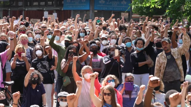 people raise their fists in solidarity as names of black lives lost are read out at a black lives matter peaceful protest in newington green with... - identity politics stock videos & royalty-free footage
