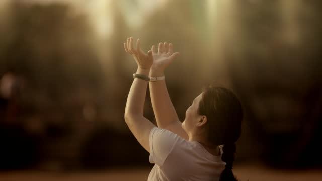 people raising arms at dawn, angkor wat - soft focus stock videos & royalty-free footage