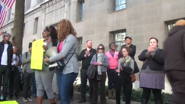 Hundreds of people attend a protest outside the Department of Justice to protest a grand jury's decision not to prosecute a police officer for...