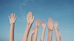 People rasing hands on blue sky background. Voting, democracy or volunteering concept