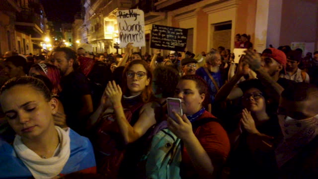 vídeos de stock e filmes b-roll de people react after hearing, while demonstrating near the governor's mansion, reports that gov. ricardo rossello will step down, on july 23, 2019 in... - cargo governamental