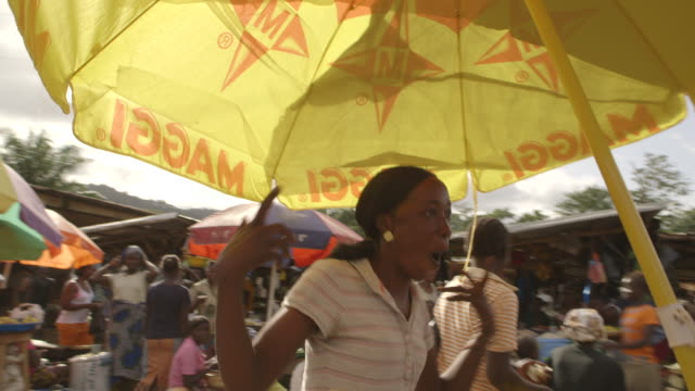 People react to the camera at a busy market in Kenema, Sierra Leone.