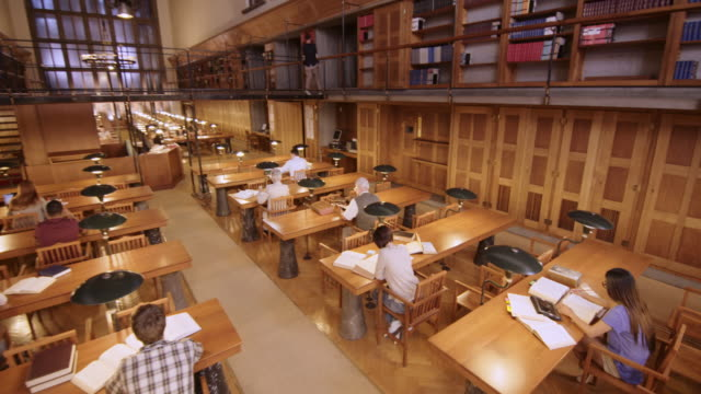 CS People reading and studying in the reading room of a library