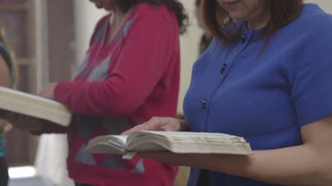 people reading bibles in tijuana church, medium shot - christianity stock videos & royalty-free footage