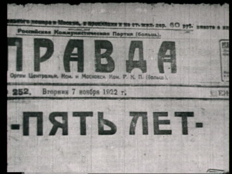 1922 montage b/w ms people reading newspapers on street/ cu soviet communist newspaper, 'pravda', and various newspaper headlines/ russia - ex unione sovietica video stock e b–roll