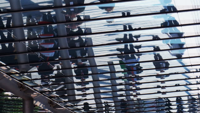 ms, people reflected in exhibit hall walkway glass roof, munich, germany - kongressversammlung stock-videos und b-roll-filmmaterial