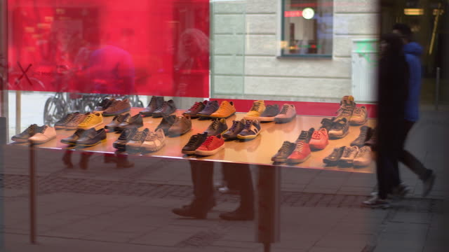 people reflected in shop window of a shoe shop, pan shot - sportschuh stock-videos und b-roll-filmmaterial