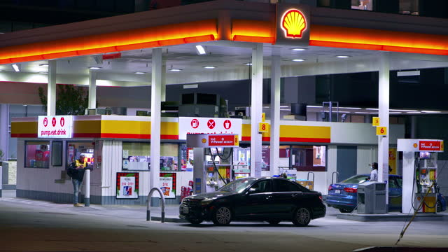 people refueling cars using unleaded gasoline at the gas station pump and convenience store at night, 4k - car stock videos & royalty-free footage