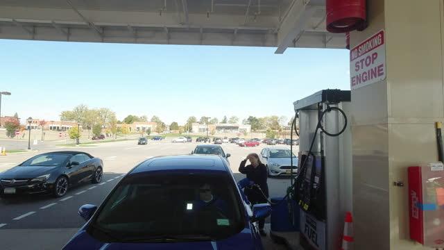 vídeos de stock e filmes b-roll de people refuelling at costco gas station in detroit amid the 2020 global coronavirus pandemic. - cadeia de lojas