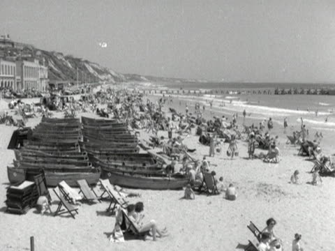 people relax and have fun on bournemouth beach - bournemouth stock-videos und b-roll-filmmaterial