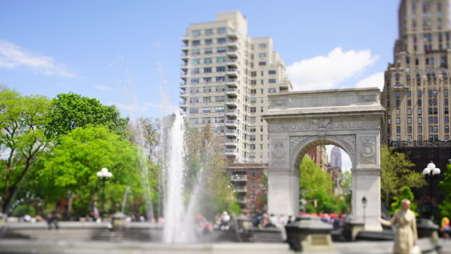 people relax and walk around the fountain in the washington square park, which is surrounded by fresh green trees at new york city ny usa on may 16 2019. - エンパイアステートビル点の映像素材/bロール