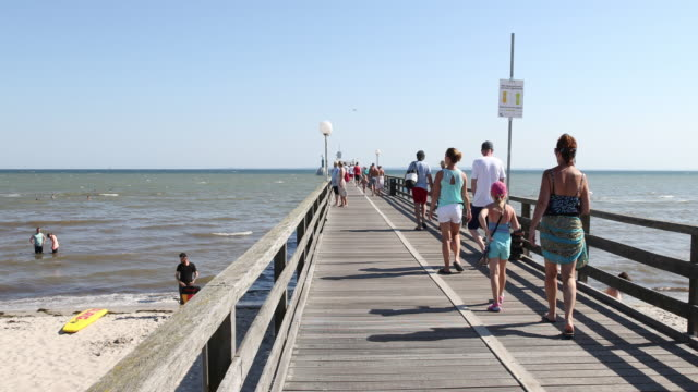 people relax and walk down a pier at the beach at high summer temperatures around 30 degrees celsius during the novel coronavirus crisis on august... - schleswig holstein stock videos & royalty-free footage