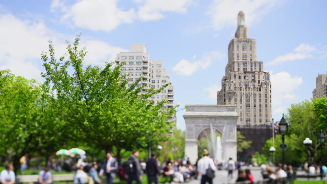 people relax and walk in the washington square park, which is surrounded by fresh green trees at new york city ny usa on may 16 2019. - エンパイアステートビル点の映像素材/bロール
