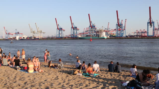 people relax at a beach at elbe river in hamburg harbour on a hot summer day with temperatures above 30 degrees during the novel coronavirus pandemic... - swimming shorts stock videos & royalty-free footage