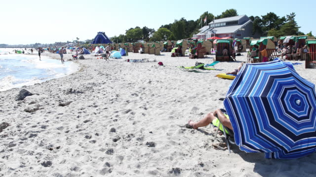 people relax at beach at high summer temperatures around 30 degrees celsius during the novel coronavirus crisis on august 13, 2020 in groemitz,... - sonnenschirm stock-videos und b-roll-filmmaterial