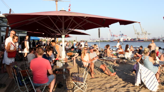 people relax at the beach and at a bar and restaurant at elbe river in hamburg harbour on a hot summer day with temperatures above 30 degrees during... - swimming shorts stock videos & royalty-free footage