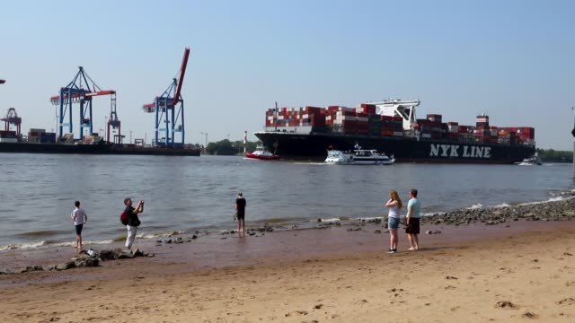vídeos de stock, filmes e b-roll de people relax on a beach as a container ship passes by on the elbe river near hamburg port on june 1 2018 in hamburg germany shipping companies that... - rio elbe