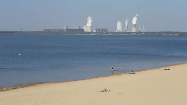 people relax on a beach at baerwalder see, an artificial lake created from a former open-pit coal mine, as the boxberg coal-fired power plant stands... - fossil fuel stock videos & royalty-free footage