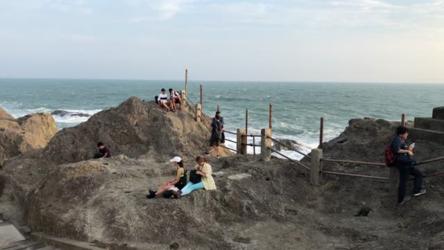 vidéos et rushes de people relax on a rocky outcrop on enoshima island on august 16 2019 in enoshima japan scheduled to host sailing events enoshima is one of a number... - outcrop